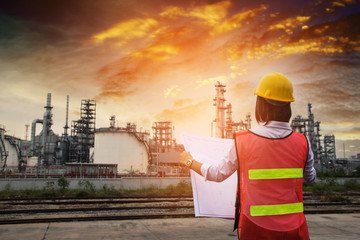 The people worker women engineer work control at power plant energy industry manufacturing oil refinery. Engineering check plant with blue print at sunset time.