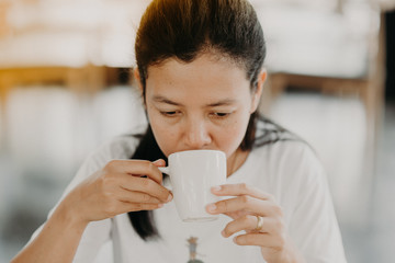 Asian girl is sitting to drink coffee at a coffee shop