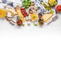 Italian food ingredients pasta olive oil parmesan cheese basil garlic mushrooms tomatoes olives on marble board