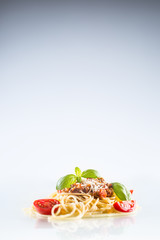Spaghetti bolognese basil tomatoes and parmesan cheese on white background
