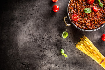 Classic italian bolognese sauce with ingredients pasta spaghetti olive oil tomatoes basil and parmesan cheese