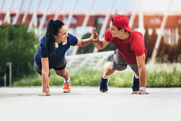 fitness, sport, people and lifestyle concept - man and woman exercising outdoors