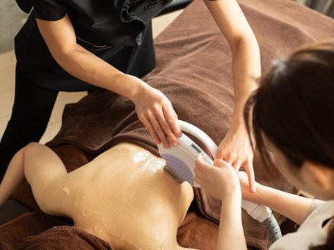 背中の脱毛で光脱毛器を扱う研修を受ける女性エステティシャン