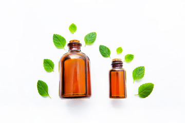 Natural Mint Essential Oil in a Glass Bottle with Fresh Mint Leaves on white over wooden background.