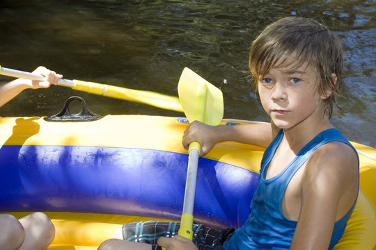 An outdoor portrait of a twelve year old boy in an inflatable boat on summer vacation.