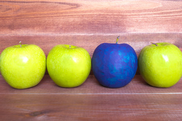 Standing out of the crowd concept, green apples and one painted blue on the wooden background.