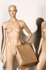 naked bald mannequin with paper bags on white