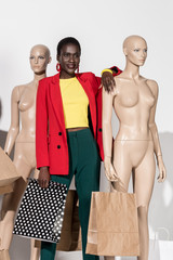 beautiful smiling african american girl standing between dummies with shopping bags on white