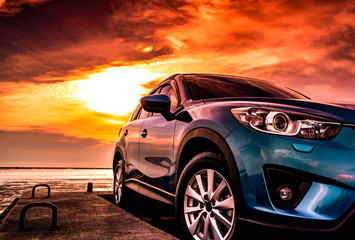Foto auf Acrylglas Rotglühen Blue compact SUV car with sport, modern, and luxury design parked on concrete road by the sea at sunset. Front view of beautiful hybrid car. Driving with confidence. Travel on vacation at the beach.