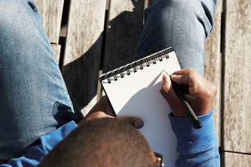 Attractive casually dressed young black male student making notes in copybook, preparing for lesson at university