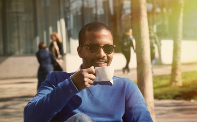 Portrait of smiling confident young African-American businessman in formal wear sitting at bench in city park and drinking hot coffee.Blurred background.Horizontal