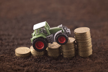Tractor miniature with coins on fertile soil land