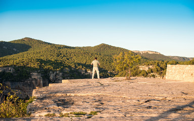 SIURANA DE PRADES, SPAIN - OCTOBER 5, 2017: A photographer with a tripod takes pictures of the landscape. Copy space for text.