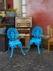 Blue chairs, flower pots and old radios at a cafe on a street in Sibiu, Romania