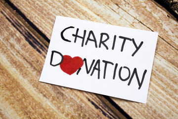 Conceptual image with Charity Donations handwritten message on the white paper with wooden background. Health and god will concept with red heart. Help for people having no money.
