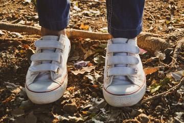 Closeup of a lady's white canvas shoe.