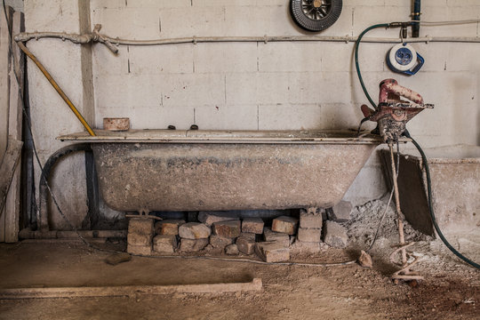 Old dirty bath standing in workshop