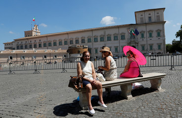 Tourists rest  in front of Quirinal Palace in Rome
