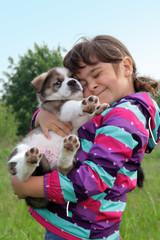 Tierliebe: Kleines Mädchen kuschelt mit Hund Welpe American Akita Mix