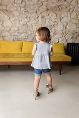 Toddler seen from behind wearing Mother's high-heel shoes and handbag