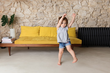 Little girl dancing in retro decorated living room