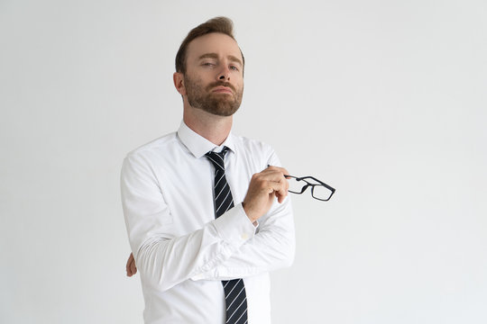 Young arrogant business expert posing for camera. Vain serious Caucasian man with pained face expression holding glasses. Self importance and ego concept
