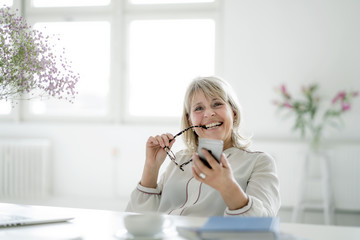 Portrait of happy mature businesswoman holding cell phone at desk