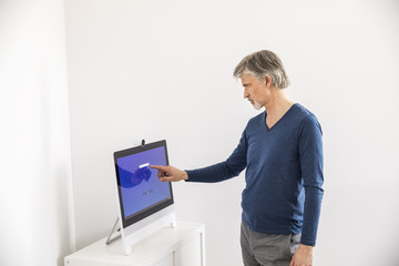 Businessman entering PIN code on touch screen