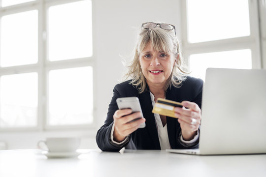 Mature businesswoman with smartphone, credit card and laptop at desk in the office