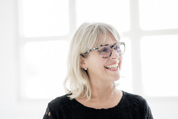 Laughing mature woman wearing glasses looking sideways