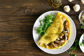 Omelette stuffed with mushrooms, pieces of chicken meat, greens
