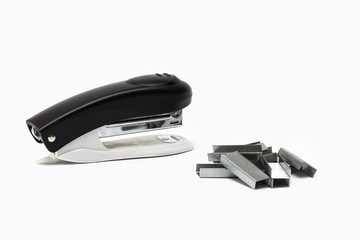 Black and white stapler and paper clip on white background