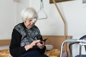 Lonley elderly 95 years old woman sitting at the bad using modern mobile phone application to monitor her therapy and entertain herself.