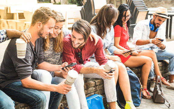Multiracial millennials group using smart phone at city college backyard - Young people addicted by mobile smartphone - Technology concept with connected trendy friends - Warm vibrance sunshine filter