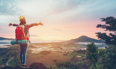 Beautiful Female tourist with backpack Happy on the hill At sunrise.