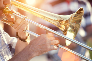 young man playing trombone on street