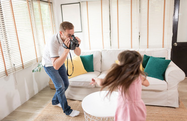 Happy holiday. Kind dad is recording video with his cute daughter and running around living room. Setup studio shooting.