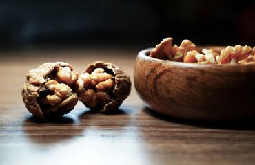 Kernel walnuts in wooden bowl with two broken walnuts on dark walnut table background.