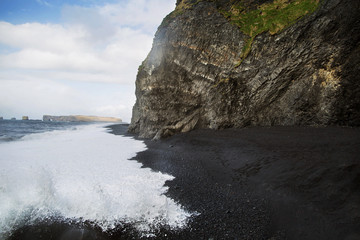 beach with black sand and hanging rock in Iceland