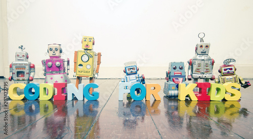 Wall mural the words CODING FOR KIDS  with rtro robot toys on a wooden floor