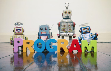 Wall Mural - the word PROGRAM with wooden letters and retro toy robots  on an old wooden floor