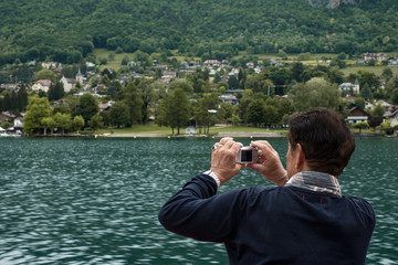 Man back portrait taking picture of Lake Annecy with compact camera