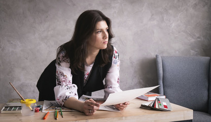 Creative professions: A woman designer reflects on the project and holds a sketch in her hands. On the table are scattered sketches, paints and brushes.