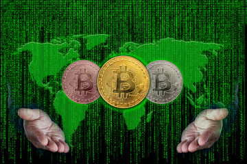 Hands of businessman holding three bitcoin metallic coin on the World map with binary code of matrix effect background.