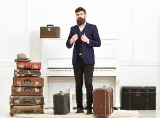 Man, traveller with beard and mustache with luggage, luxury white interior background. Macho elegant on strict face stands near pile of vintage suitcase, ready for vacation. Luggage and travel concept