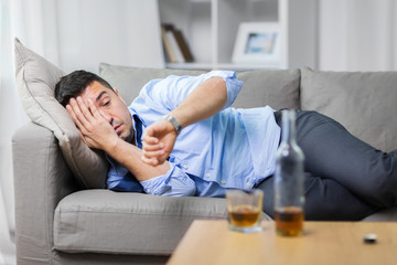 alcoholism, alcohol addiction and people concept - male alcoholic lying on sofa and looking at wristwatch