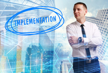 The concept of business, technology, the Internet and the network. Young businessman showing inscription: Implementation
