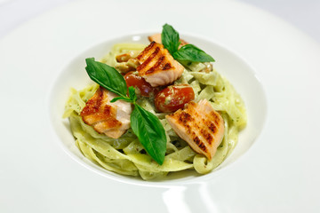 Italian pasta fettuccine with salmon and tomatoes on a white plate