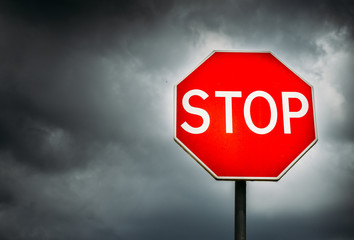 Conceptual stop sign with stormy background and copy space