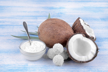 Coconut with coconut sweets and fresh coconut oil on a blue wooden background